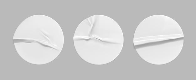 白い丸いしわくちゃのステッカーモックアップセット。接着しわの効果がある粘着性の白い紙またはプラスチックステッカーラベル。 Premiumベクター