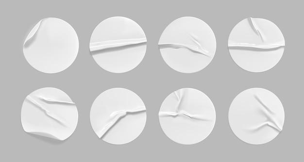 Набор белых круглых мятых наклеек. клейкая белая бумага или пластиковый стикер с наклеенным, морщинистым эффектом на сером фоне. пустые шаблоны этикеток или ценников. 3d реалистично. Premium векторы