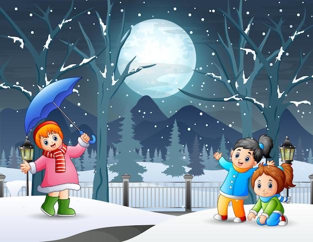 子供たちが屋外で遊ぶ冬の夜の風景 Premiumベクター