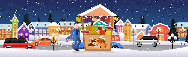 Женщина покупает подарочную коробку в прилавке с подарками рождественский рынок зимняя ярмарка концепция счастливого рождества праздники современный город улица городской пейзаж фон полная длина эскиз горизонтальный векторная иллюстрация Premium векторы