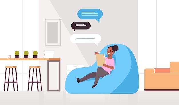 モバイルアプリのソーシャルネットワークチャットバブル通信を使用して豆袋に座っているメッセージングアフリカ系アメリカ人の女の子のチャットの女性 Premiumベクター