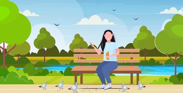 女性のパンを保持しているとハトの肥満の女の子の群れに餌をやる楽しんで屋外の公共公園の風景の背景フラット全長水平の木製のベンチに座っている太りすぎの少女 Premiumベクター