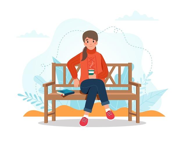 コーヒーカップとベンチに座っている秋の女性 Premiumベクター