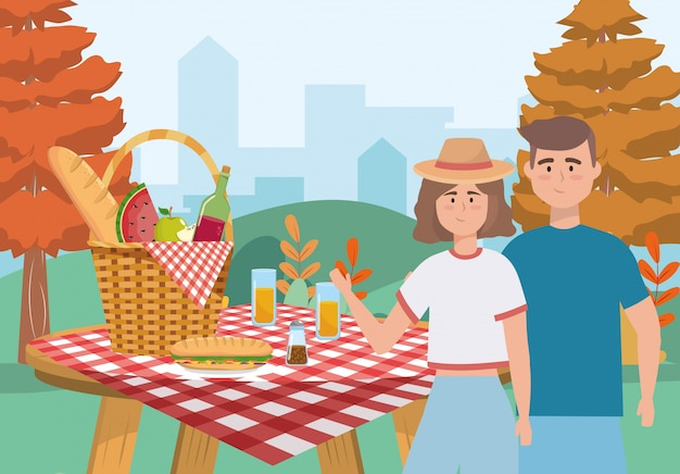 Woman and man couple with hamper and food Free Vector