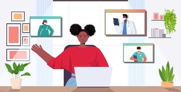 Webブラウザーで混合レース医師と話し合う女性患者 Premiumベクター
