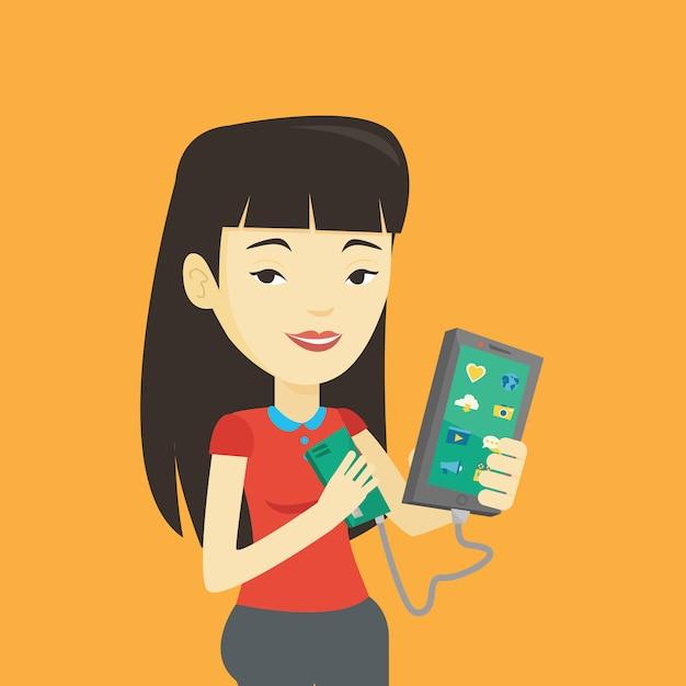 Woman reharging smartphone from portable battery. Premium Vector