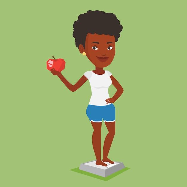 Женщина, стоя на шкале и держа в руке яблоко. Premium векторы
