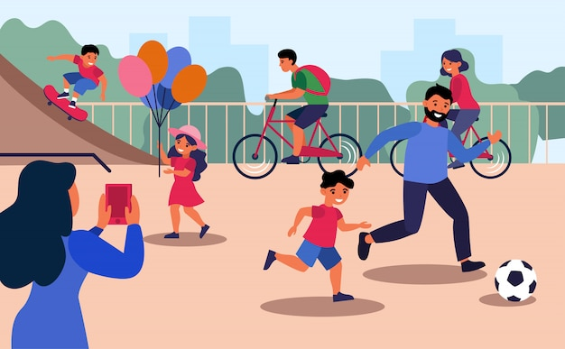 Woman taking selfie of her family having fun on playground Free Vector