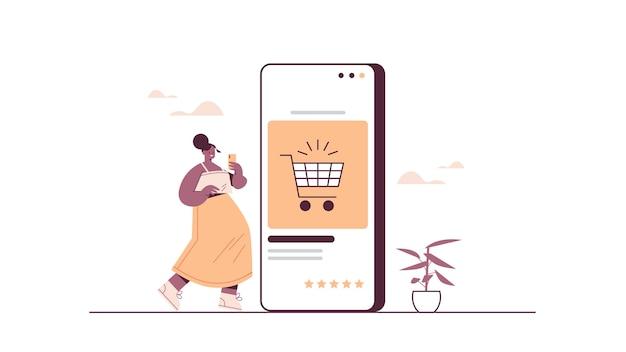 スマートフォンを使用してオンラインストア販売消費者のオンラインショッピングeコマーススマート購入で物事を購入する女性 Premiumベクター