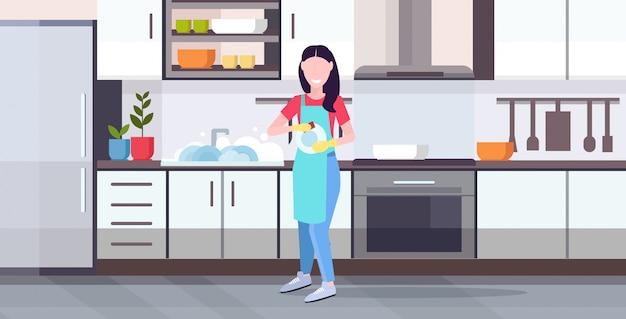 Женщина моет посуду домохозяйка вытирает тарелки полотенцем концепция мытья посуды девушка в фартуке делает работу по дому современная кухня интерьер горизонтальный квартира полная длина Premium векторы