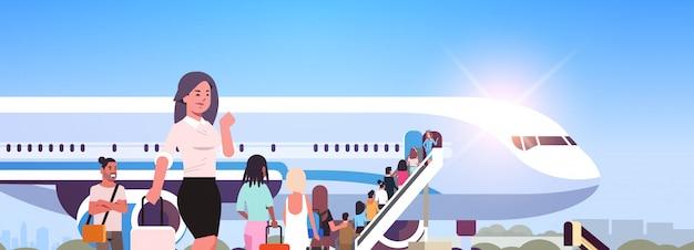 飛行機の背面ビューの乗客が飛行機の搭乗旅行の概念に搭乗するはしごを登るに行く人々の旅行者の荷物立っているラインキューを持つ女性 Premiumベクター