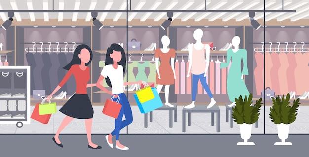 Женщины несут хозяйственные сумки девочки пара весело вместе гулять праздник большой продажа концепция современный бутик мода магазин экстерьер полная длина горизонтальный Premium векторы