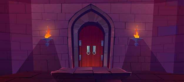 Деревянная дверь в средневековом замке. старые ворота в каменной стене с пылающими факелами ночью. Бесплатные векторы
