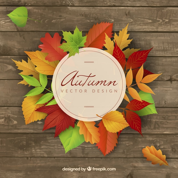 Wooden background with colored autumnal leaves Free Vector