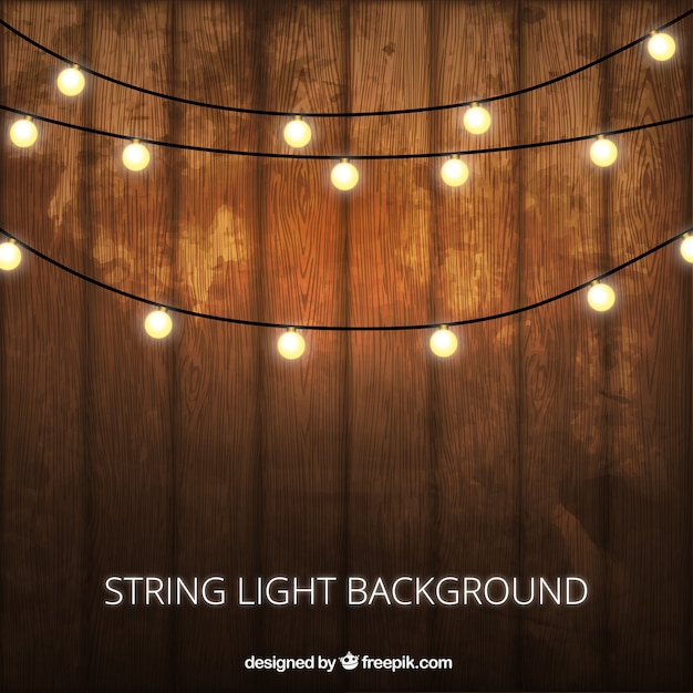 Wooden background with decorative lightbulbs Free Vector