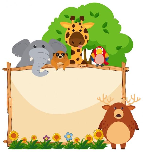 Wooden frame with wild animals in garden Free Vector
