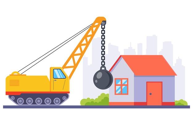 Желтая строительная техника сносит старый дом большим металлическим шаром. Premium векторы