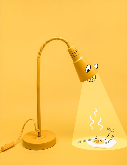 Yellow lamp character illuminating a fried egg Free Vector