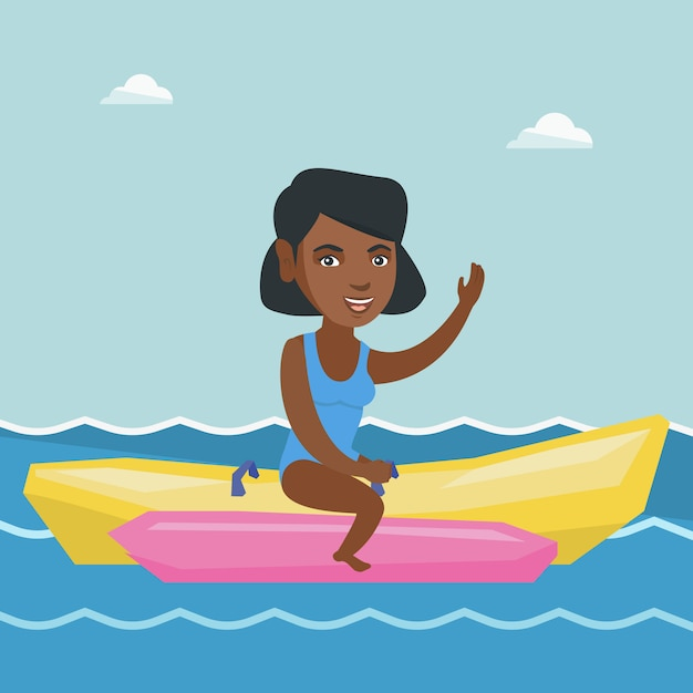 Young african-american woman riding a banana boat. Premium Vector
