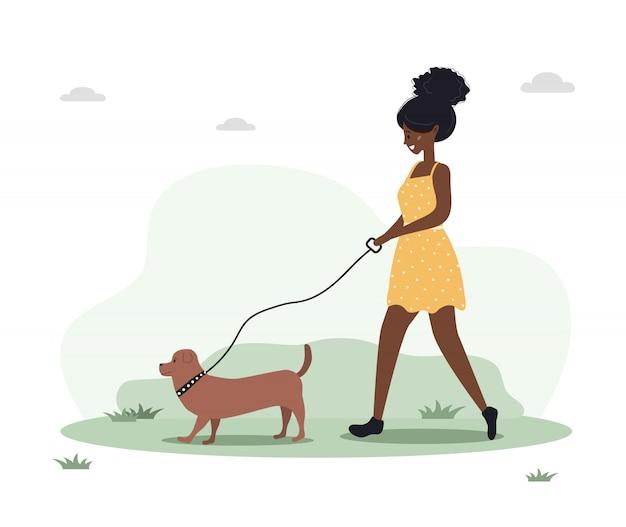若いアフリカ人女性は森の中を犬と一緒に歩きます。ダックスフントやプードルと黄色のドレスでコンセプトハッピーガール。フラットスタイルのベクトル図です。 Premiumベクター
