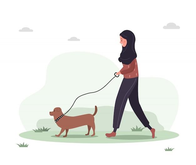ヒジャーブの若いアラブ女性が森の中を犬と一緒に歩きます。ダックスフントやプードルと黄色のドレスでコンセプトハッピーガール。フラットスタイルのベクトル図です。 Premiumベクター