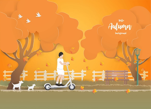 A young boy riding an electric scooter in the park on the grass in autumn. Premium Vector