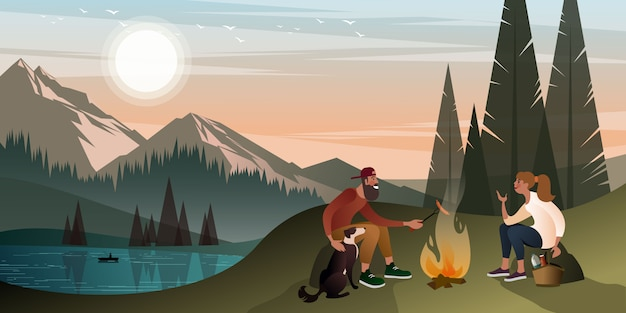 Young couple with a dog on a halt near a campfire in the mountains on a warm summer evening. Premium Vector