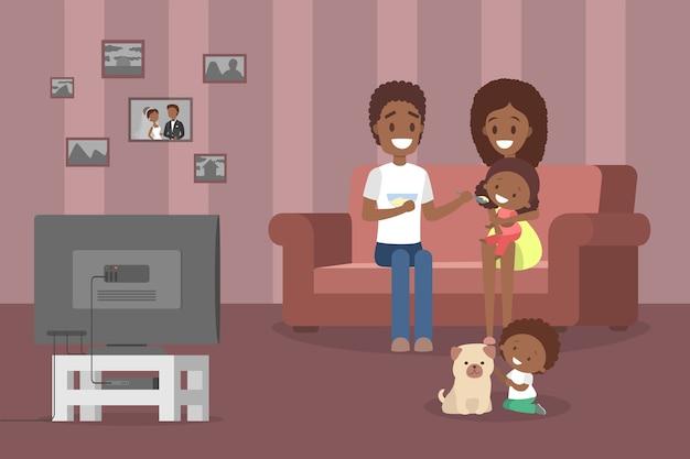 リビングルームでテレビを見て一緒に時間を過ごす若いかわいい家族。父と母は自分の小さな娘を養います。犬と遊ぶ少年。図 Premiumベクター