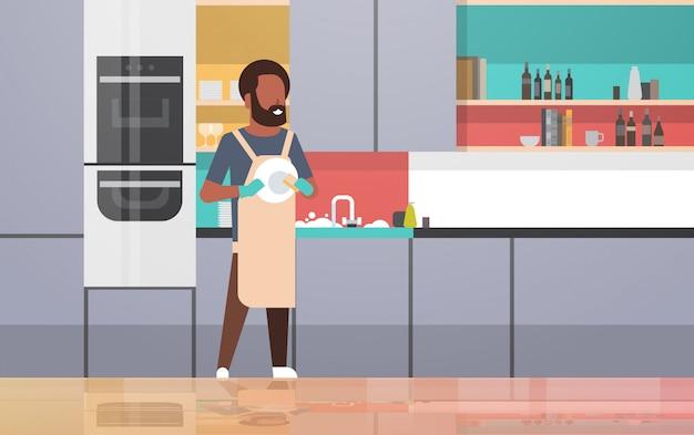 Молодой человек мыть посуду парень вытирая тарелки делать по дому концепция мытья посуды современная кухня интерьер горизонтальный полная длина Premium векторы