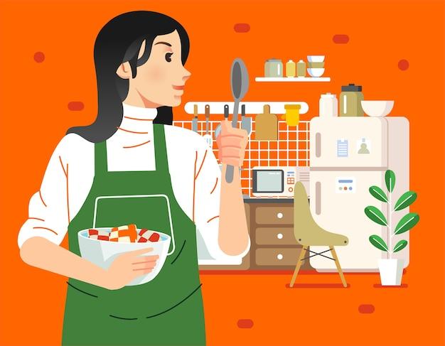 Молодая мама готовит на кухне, она держит миску и ложку с кухонным интерьером как фоновую иллюстрацию. используется для плакатов, веб-изображений и прочего Premium векторы