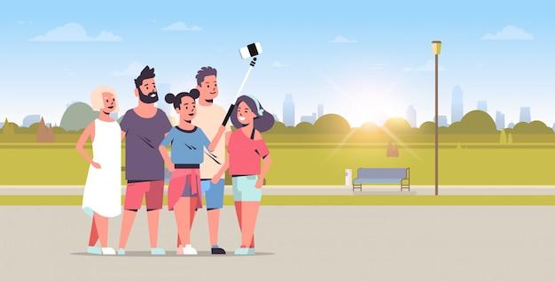 Группа молодых людей, используя селфи палку, принимая фото на смартфон камеры друзей, стоя вместе город городской парк восход пейзаж фон горизонтальный вектор иллюстрация Premium векторы