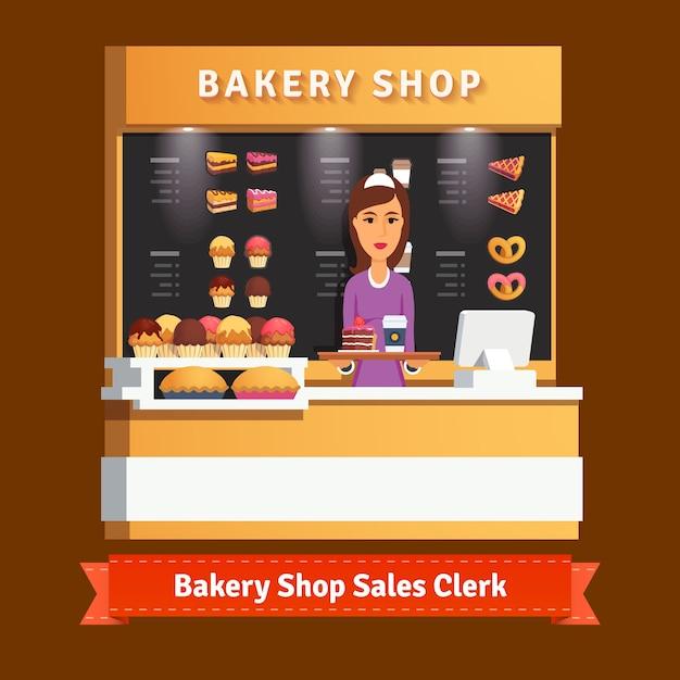 Young shop woman assistant at the cashier desk