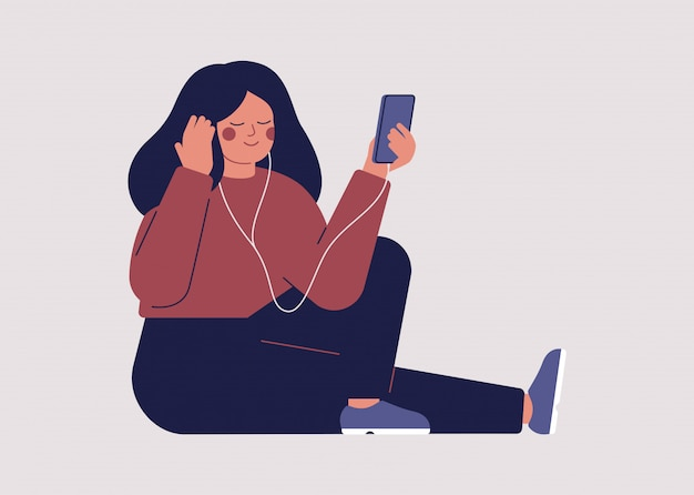Young woman is listening to music or an audiobook with headphones on her smartphone. Premium Vector