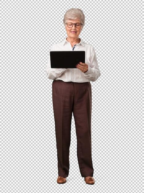 Ältere frau des vollen körpers lächelnd und überzeugt, eine tablette halten, sie verwendend, um das internet zu surfen und social media zu sehen, kommunikationskonzept Premium PSD