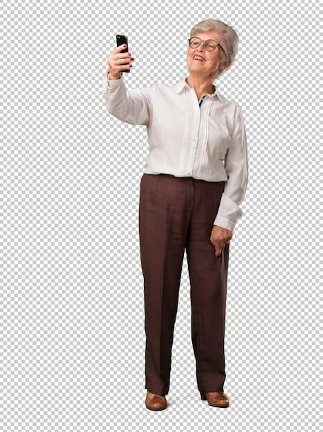 Ältere frau des vollen körpers überzeugt und nett, ein selfie nehmend und betrachten das mobile mit einer lustigen und sorglosen geste und surfen die sozialen netzwerke und das internet Premium PSD