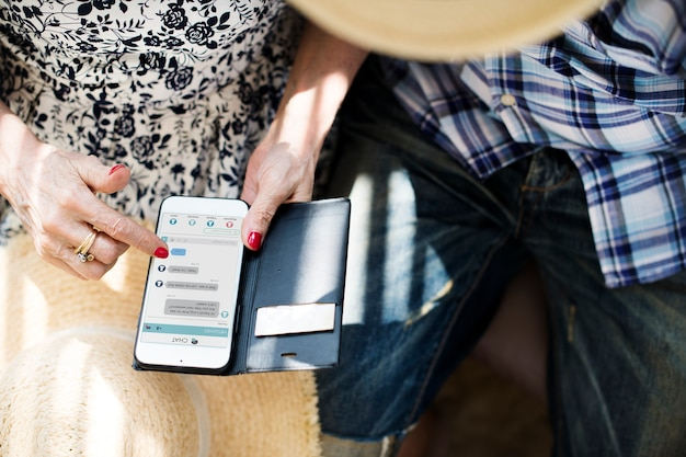 Ältere frau, die ihr mobile verwendet Premium PSD