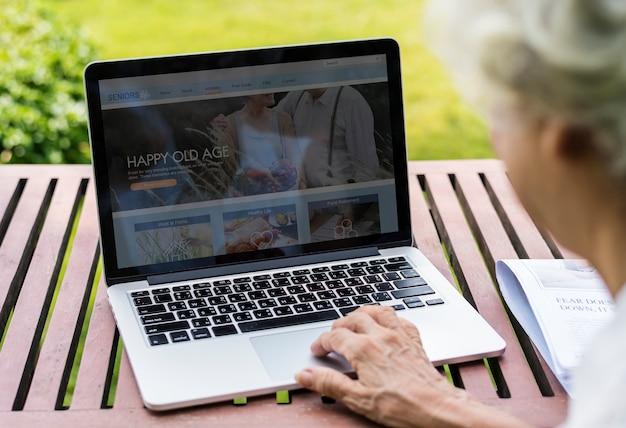 Ältere frau, die im urlaub einen laptop verwendet Kostenlosen PSD