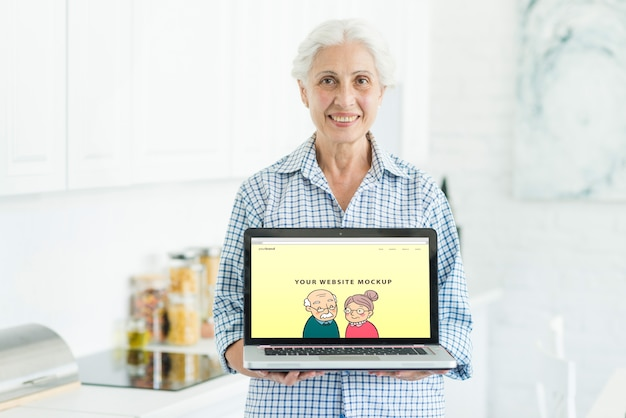 Ältere frau, die laptopmodell hält Kostenlosen PSD