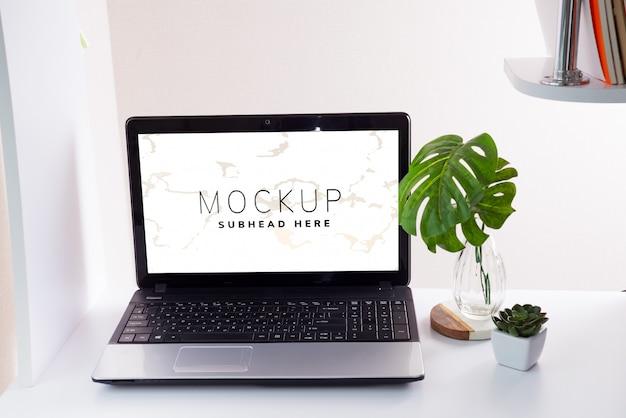 Arbeitsplatz mit laptop- und monsterablättern Premium PSD