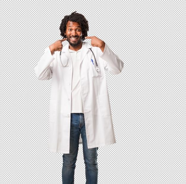 Arzt des hübschen afroamerikaners lächelt und zeigt mund, konzept von perfekten zähnen, weiße zähne, hat eine nette und gemütliche haltung Premium PSD