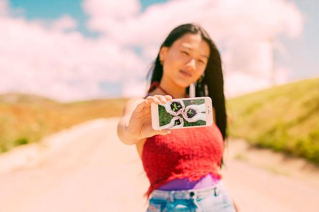 Asiatin, die smartphonemodell in der natur darstellt Kostenlosen PSD