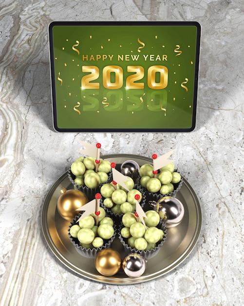 Behälter mit schokolade neben tablette mit mitteilung des neuen jahres Kostenlosen PSD