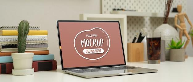 Beschnittene aufnahme des arbeitsplatzes mit modell laptop, bücher, briefpapier und dekorationen auf weißem tisch Premium PSD