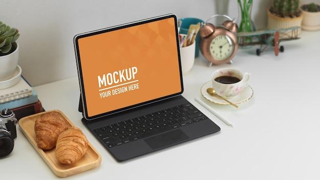Beschnittene aufnahme von home office mit digitalem tablet, dekorationen, croissant und kaffee Premium PSD