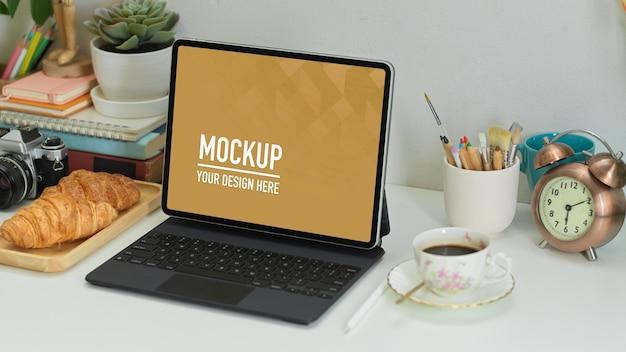 Beschnittene aufnahme von home office mit digitalem tablet, zubehör, croissant und kaffee Premium PSD