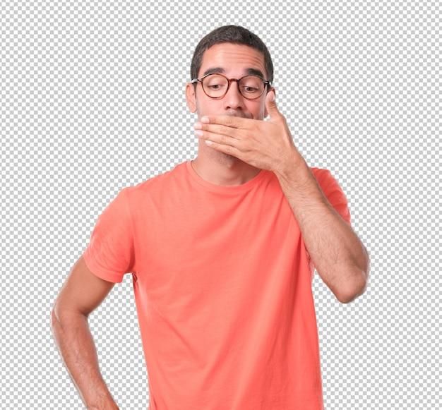 Besorgter junger mann, der seinen mund mit seiner hand bedeckt Premium PSD