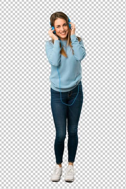 Blonde frau mit blauem hemd hörend musik mit kopfhörern Premium PSD