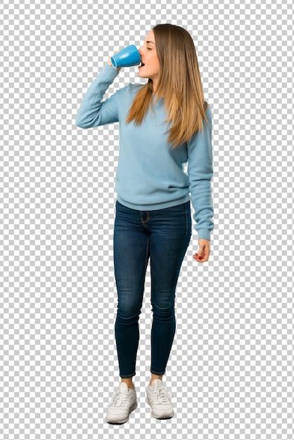 Blonde frau mit dem blauen hemd, das einen heißen tasse kaffee hält Premium PSD