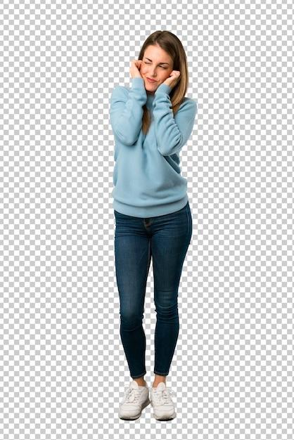 Blonde frau mit den blauen hemdbedeckungsohren mit den händen. frustrierter ausdruck Premium PSD
