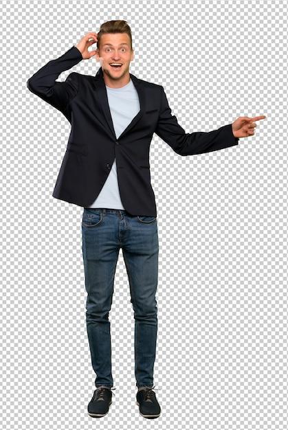 Blonder gutaussehender mann überrascht und finger auf die seite zeigen Premium PSD